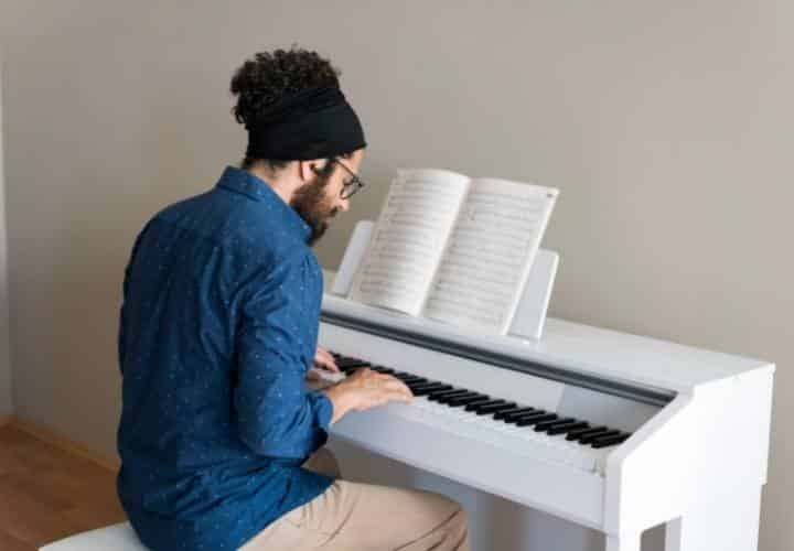 Preparation - Man playing on an upright digital piano